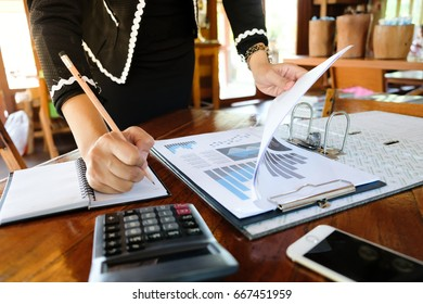 Right-hand woman finance Hold a pencil. Left hand open graph data. To summarize monthly sales on the desk.