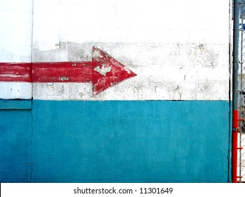 right-pointing arrow in chipped, flaking red paint on a white and blue wall