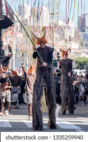 Rijeka, Croatia,3.3.2019: people dressed in minotaur costumes walking on stilts and carrying long poles in the street with streamers and crowds in the background as part of Rijeka Carnival 2019