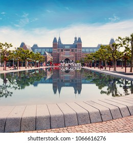 Rijksmuseum Amsterdam museum with words I Amsterdam and a fountain with building reflection in the water in the foreground