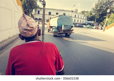 Rikshaw driver on a road. View from passanger seat.