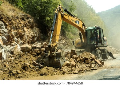 Rila Monastery, Bulgaria - July 30, 2016: Construction work to expand the mountain road. The work of modern road-building equipment. Narrow Passage. Closed road. Repair work on the highway