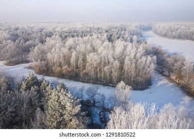 Rime and hoarfrost covering trees. Aerial view of the snow-covered forest and lake from above. Winter scenery. Landscape photo captured with drone.