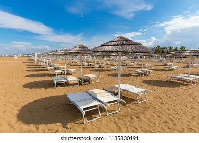 Rimini beach. Sun umbrellas and deck chairs on sand. Blue sky over beach. Italy resort.