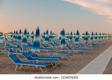 Rimini beach. Beach umbrellas and deck chairs on sand in the evening.