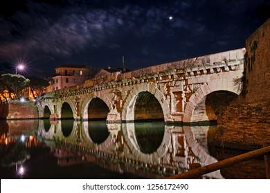 Rimini, Emilia Romagna, Italy: the ancient Roman bridge of Tiberius at night in the picturesque old town