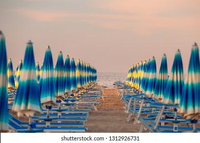 Rimini, Italy. Rimini beach with blue sun umbrellas in the evening. Rimini seaside. Famous resort in Italy.