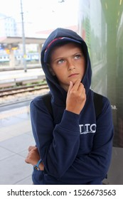 Rimini, Italy, July 2019. Portrait Thoughtful young boy in hood touching  chin with finger thinking or considering. Pensive Boy making decision or imagining