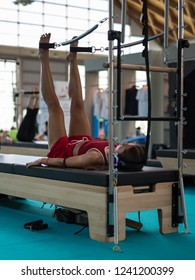 Rimini, Italy - june 2018: Girl with Headphones Lying on Bed doing Exercises with Legs Traction Training Equipment at Gym.