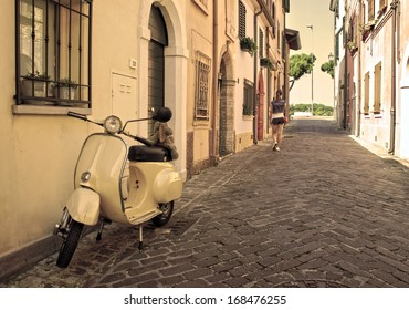 RIMINI, ITALY - June 30: Vintage scooter parked in a typical narrow old street in Rimini, June 30, 2013 Rimini, Italy. This is the preferred way to travel in old narrow streets of Italy