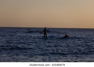 RINCON, PUERTO RICO - February 16th 2016 - A young surfer silhouetted against the setting sun at Domes Beach. Rincon is a popular surfing destination for tourists in the winter months.