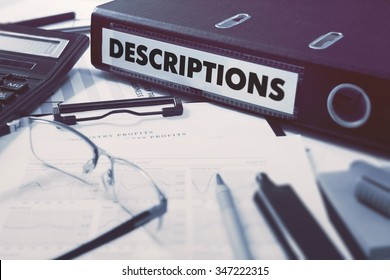 Ring Binder with inscription Descriptions on Background of Working Table with Office Supplies, Glasses, Reports. Toned Illustration. Business Concept on Blurred Background.
