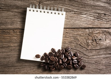 ring binder paper note book with coffee beans on space of old wood plank