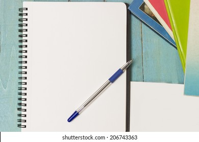 Ring binder, pen and a stack of books. Writing material ready to take notes, do homework or research. Directly above