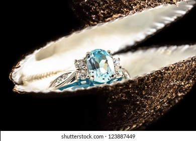 Ring with blue stone in a shell on black background