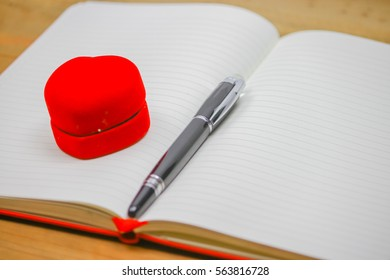 Ring box and pen on open note book
