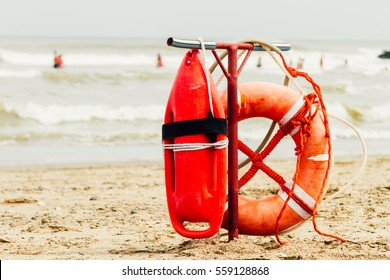 Ring buoy and can of lifeguard on the beach with sea with people in the background