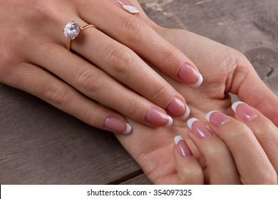 Ring with a diamond on a woman's finger. French manicure on a old wooden background.