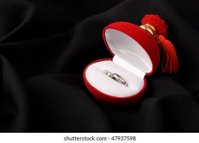 Ring and ear rings in red box on black background
