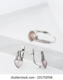 A ring and an earrings collection with lot of small diamonds and beautiful huge cut rose quartz gems.