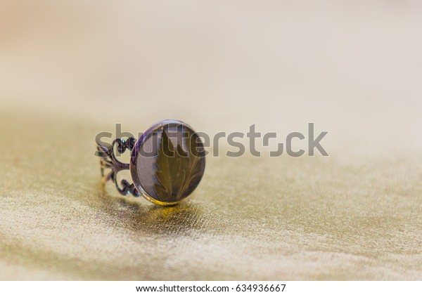 Ring with flower inside of crystal made of epoxy resin close-up with bokeh on toned background shallow depth of field