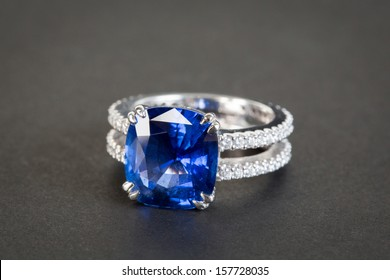 Ring of the jeweler with dark blue sapphire on the black background