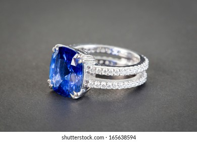 Ring of the jewelry with dark blue sapphire on the black background