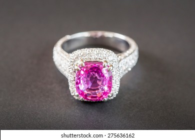 Ring of the jewelry with pink sapphire isolated on black background