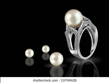 Ring with pearl and diamonds on black background
