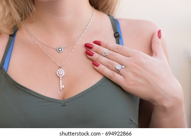 Ring, phalanx ring on a female hand ,and set of luxurious chains with pendants-silver key and white gold disk