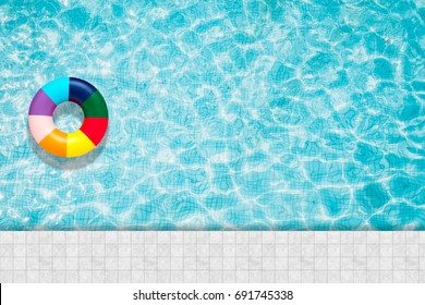 Ring pool float, floating in a refreshing blue swimming pool with towel, sun glasses and flops on the edge of pool