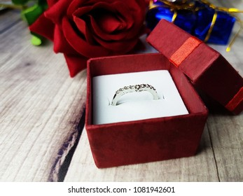 A ring in red box with red rose on wooden background