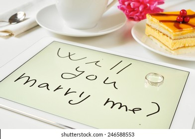 a ring and the sentence will you marry me? written in a tablet on a table at dessert time