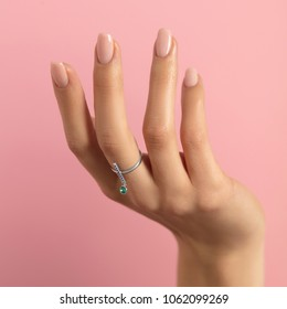 Ring of silver  with crystals in the form of an exclamation mark, precious stones of blue and turquoise, on the hand with a manicure on a beautiful model