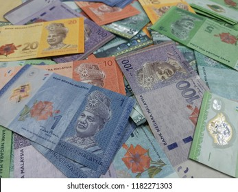 Ringgit Malaysia notes of various values are scattered on the table.