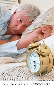 Ringing alarm clock and sleepy pensioner looking at it