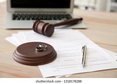 Rings with decree of divorce and judge gavel on table
