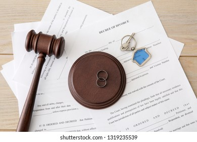 Rings with decree of divorce, judge gavel and key from house on table. Concept of dividing marital property