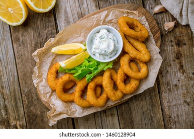 Rings of squid in batter with sauce and lemon on wooden background