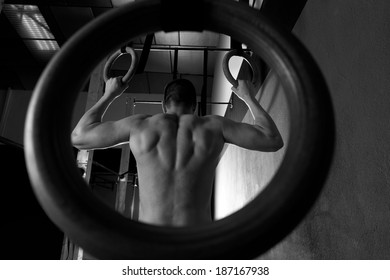 Rings workout man at gym hanging rear back view