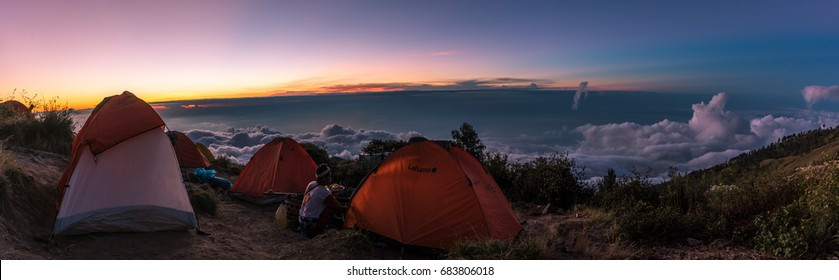 Rinjani, Lombok/Indonesia -30-06-2017- Tents on the rim of the mount Rinjani or Gunung Rinjani. The mount Rinjani is an active volcano in Indonesia on the island of Lombok. Panorama taken at sunset.