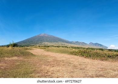 Rinjani mountain and savannah field with blue clear sky.