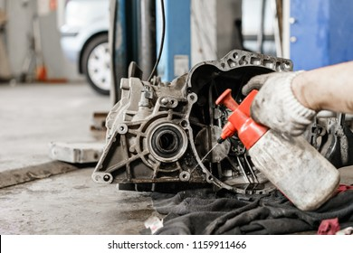rinse clutch unit after the leaking of engine oil. Change and repair clutch, drive axle. working underneath a lifted car. Professional mechanic work maintenance car. Garage car service.