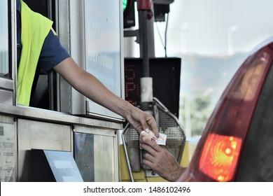 Rio Antirio, Greece - 20 August 2019 14:30 : Rio Antirio Bridge tolls. A man payed his fee and resiving a receipt and 10 euros note as change