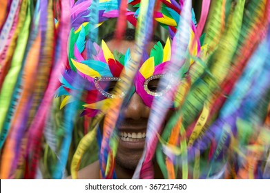 Rio Carnival scene features smiling Brazilian man in colorful mask with streamers in motion blur