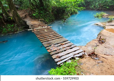 Rio celeste and small wooden bridge Tenorio national park Costa Rica