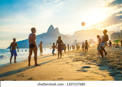 RIO DE JANEIRO - APRIL 01, 2014: Groups of young Brazilians play keepy uppy beach football, or altinho, at sunset on the shore of Ipanema Beach at Posto Nove.