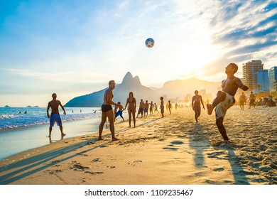 RIO DE JANEIRO - APRIL 01, 2014: Groups of young Brazilians play keepy uppy beach football, or altinho, at sunset on the shore of Ipanema Beach at Posto 9.