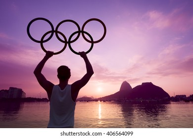 RIO DE JANEIRO - APRIL 2, 2016: Silhouette of an athlete holds Olympic rings at a colorful sunrise scene in front of Sugarloaf Mountain