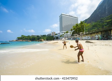 "RIO DE JANEIRO - APRIL 2, 2016: Brazilians play paddle ball (known locally as ""frescobol"") near the Sheraton Hotel, which tried unsuccessfully to privatize Vidigal Beach when it opened in 1967."